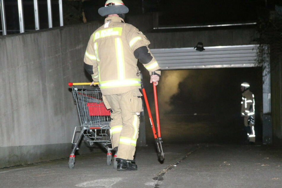 Ein Feuerwehrmann geht in die stark verrußte Tiefgarage.