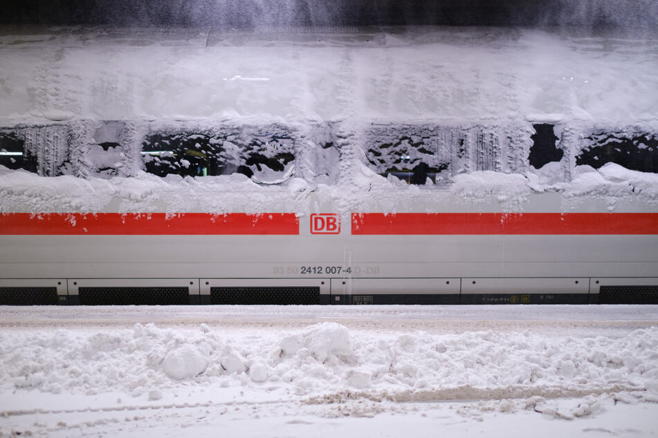 Im Hauptbahnhof Hannover steht ein verschneiter ICE. In vielen Teilen Deutschlands gibt es am Montag Einschränkungen im Bahnverkehr.