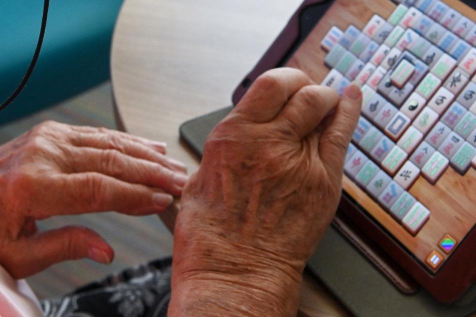 Eine Frau spielt im Seniorenheim mit ihrem Tablet Mahyong.