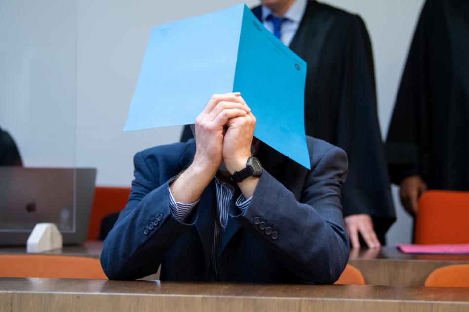 Der wegen sexuellen Missbrauchs von Kindern und Schutzbefohlenen sowie sexueller Nötigung angeklagte Mann (r) sitzt vor Prozessbeginn im Landgericht. (Archiv)