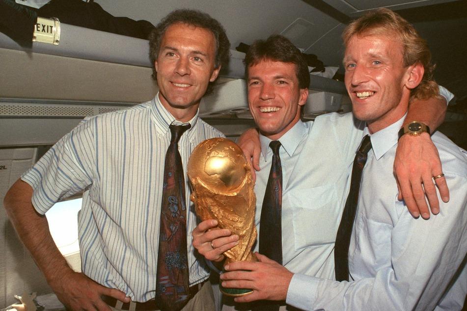 Finaltorschütze Brehme (r.) posiert 1990 an der Seite von Kapitän Lothar Matthäus (heute 60, M.) und Bundestrainer Franz Beckenbauer (heute 75, l.) mit dem WM-Pokal. (Archivfoto)
