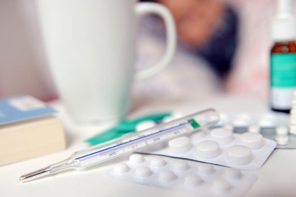 Eine Person liegt mit einer Influenza im Bett. Auf dem Nachttisch stehen Arzneimittel. (Symbolbild)