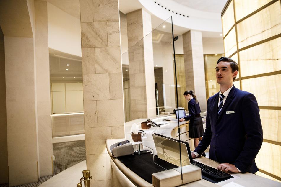 Ein Mitarbeiter steht hinter einer Schutzscheibe an der Rezeption in der Lobby im Hotel Adlon Kempinski am Pariser Platz in Berlin.