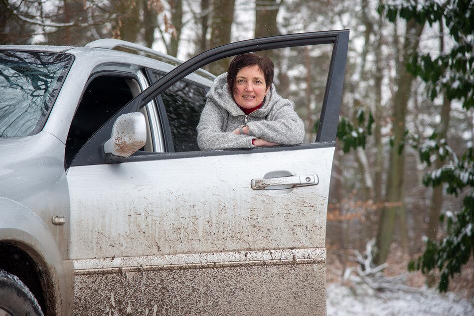 Sonja Reuter-Höling lehnt auf einem Waldweg an einem Allrad-Fahrzeug. Der Landkreis Trier-Saarburg hat das Geländeauto nach einem Erdrutsch, der den Ortsteil Hochmark von anderen Orten abgeschnitten hat, zur Verfügung gestellt.