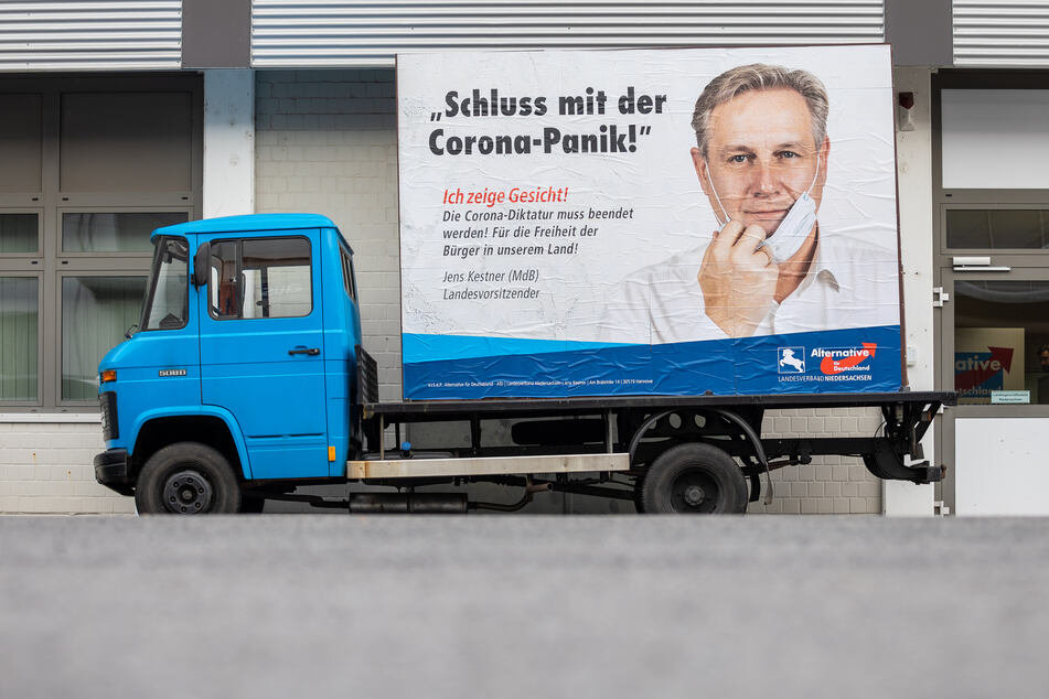 """Ein Plakatwagen der AfD zeigt ein Portät von Jens Kestner, Landesvorsitzender der AfD Niedersachsen, und den Schriftzug """"Schluss mit der Corona-Panik!""""."""