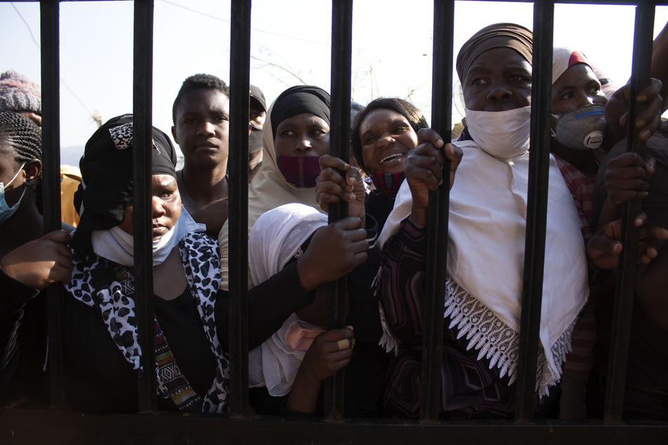 """Frauen mit Mundschutz stehen am Gitter der Squattersiedlung """"Brazerville"""". Der Stadtrat und Mitglieder der Nichtregierungsorganisation """"Lajpaal Foundation"""" trafen in dem Quartier ein, um Lebensmittelpakete zu verteilen, wo bereits Tausende von Menschen darauf warteten."""