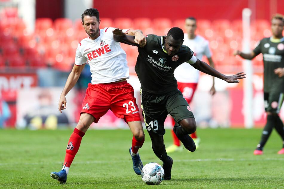 Kölns Stürmer Mark Uth (l.) und Mainz-Verteidiger Moussa Niakhate kämpfen um den Ball.