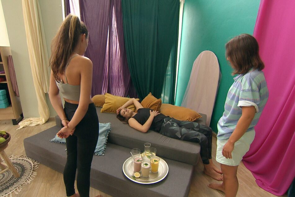Weil es ihr übel wird, muss sich Irina (M.) kurz hinlegen, während sich Lou (l.) und Miri (r.) Sorgen machen.