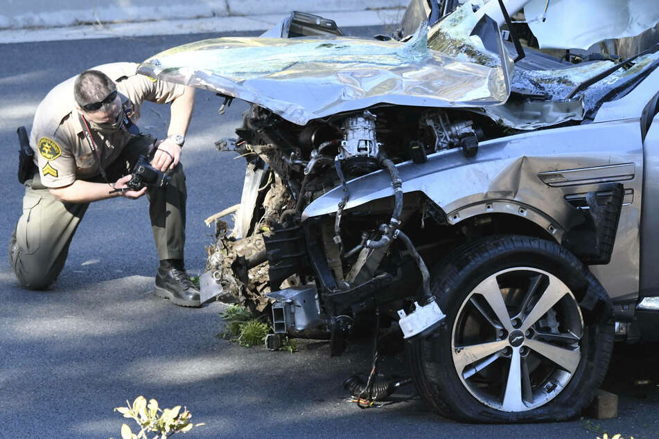A police officer documents the damage to Woods' car.