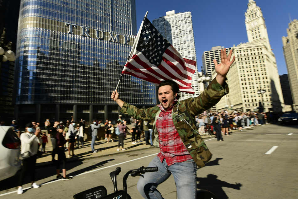 Ein Unterstützer des designierten Präsidenten J. Biden feiert beim Radfahren vor dem Trump Tower.
