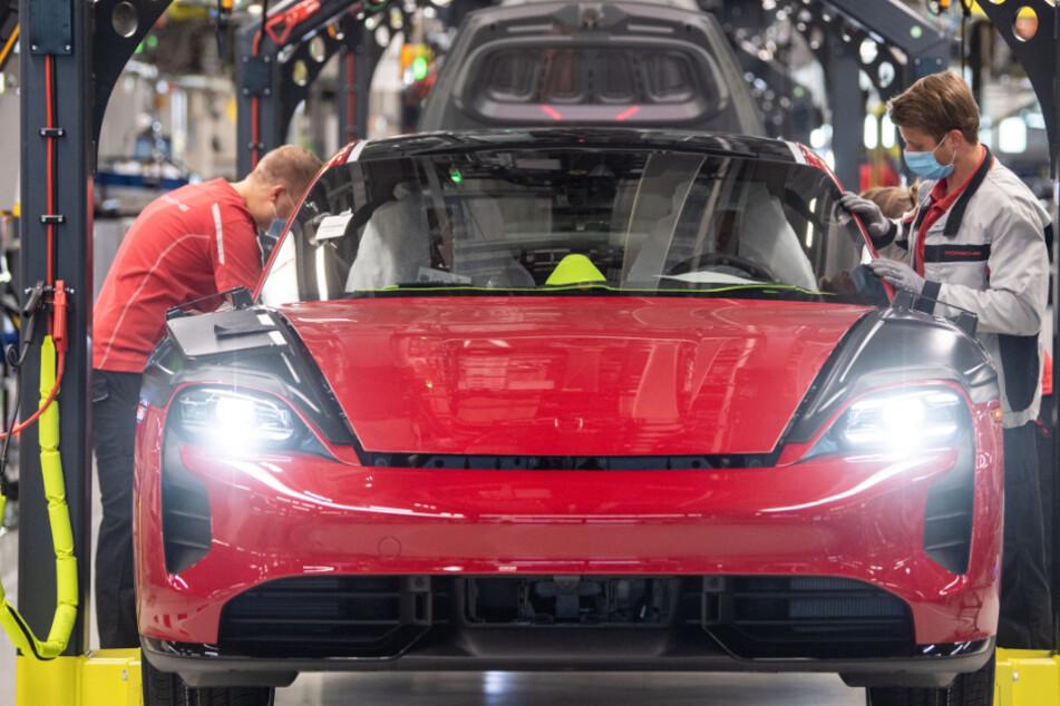Mitarbeiter der Porsche AG tragen in der Produktion des elektrisch angetriebenen Porsches Taycan Masken