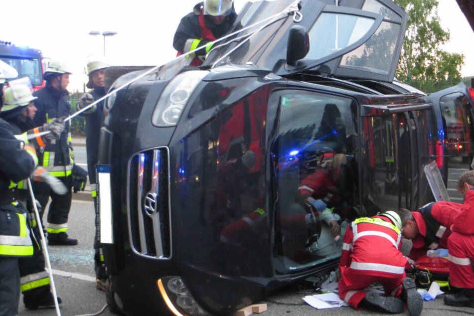 Die Feuerwehrleute versuchen, den Fahrer aus seinem Auto zu befreien.