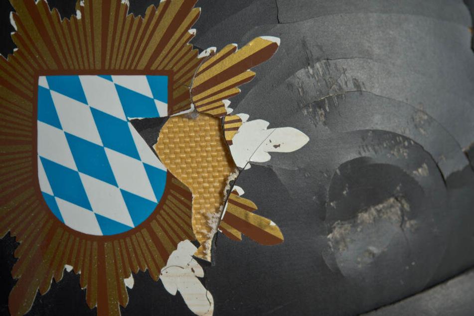 Nahaufnahme eines Polizeihelms, der durch einen Steinewerfer stark beschädigt wurde. Immer wieder kommt es zu Übergriffen auf Polizeibeamte im Einsatz. (Archivbild)