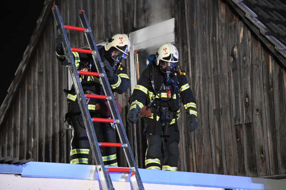 Feuerwehrleute mit Atemgerät kommen betreten das Dach des Hauses.
