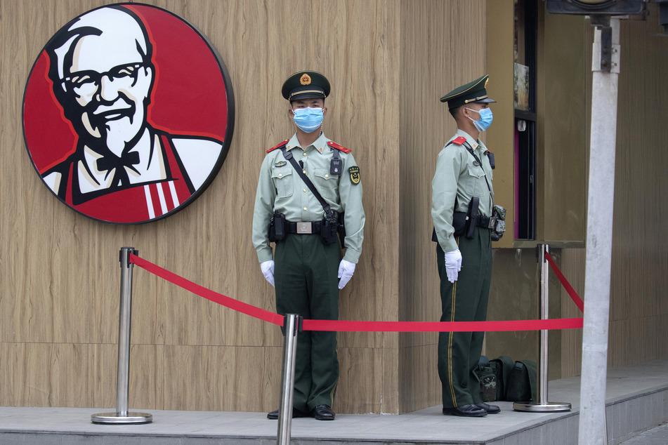 Paramilitärische Polizisten, die Mundschutzmasken tragen, um die Ausbreitung des Coronavirus einzudämmen, stehen in der Nähe eines KFC-Logos in Peking Wache, bevor die Eröffnungssitzung des Nationalen Volkskongresses in der Großen Halle des Volkes beginnt. Der Nationale Volkskongress ist Chinas Parlament.