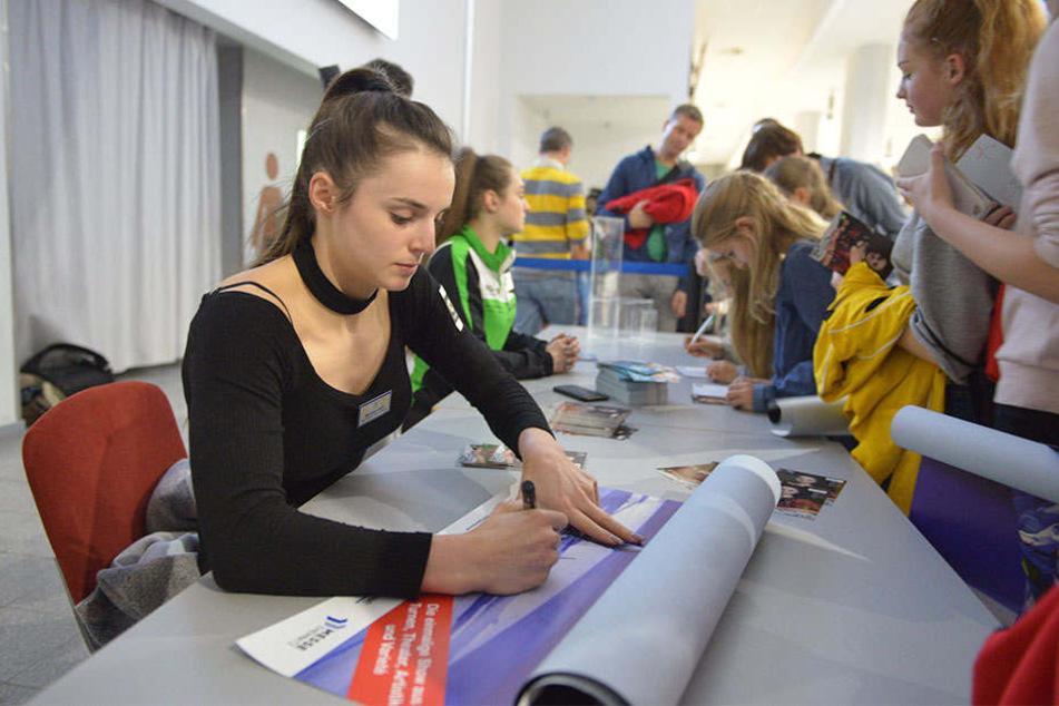 """Die Chemnitzer Turnweltmeisterin Pauline Schäfer (20) in der """"Gymmotion""""-Pause beim Autogrammeschreiben."""
