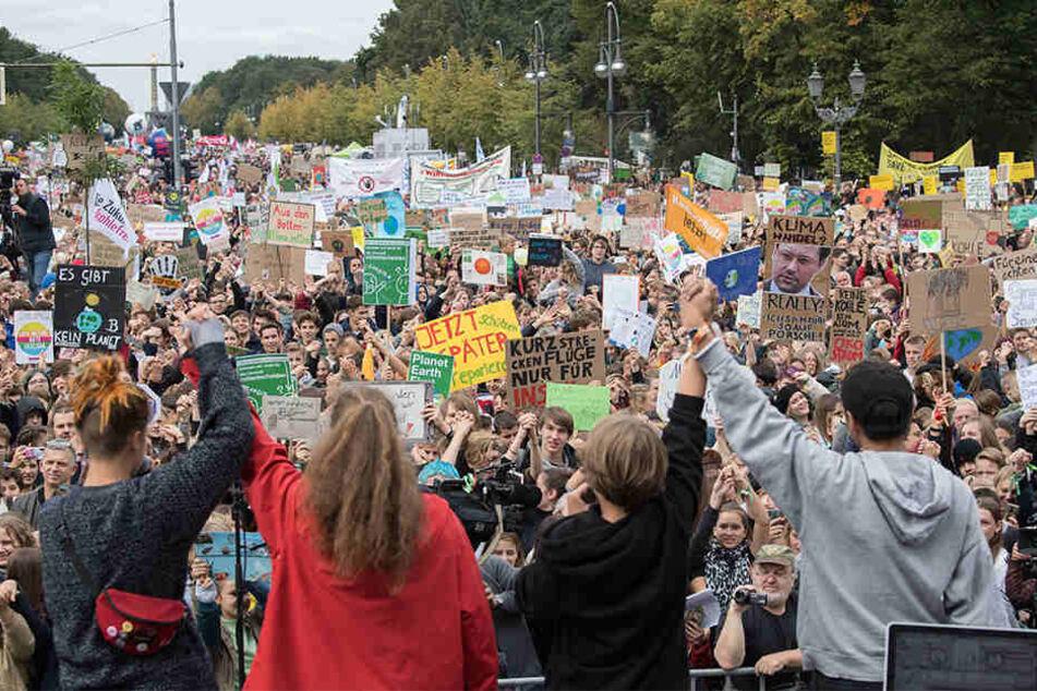 Demonstranten nehmen am Klima Protesttag von Fridays For Future vor dem Brandenburger Tor teil und stehen vor der Bühne.