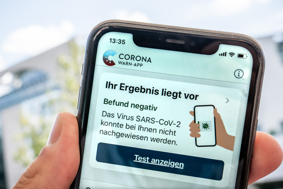 """Ein für einen Reiserückkehrer durchgeführter Corona-Test wird auf dem Display eines Iphone in der Corona Warn App als """"negativ"""" dargestellt."""