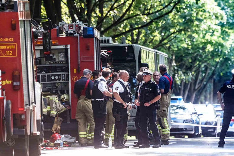Einsatzkräfte stehen vor dem Bus im Lübecker Stadtteil Kücknitz, in dem am Nachmittag ein Fahrgast Mitreisende mit einem Messer attackiert hatte.