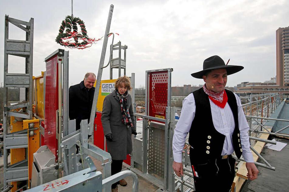 Kölns Oberbürgermeisterin Henriette Reker (parteilos, m) mit dem Architekten Felix Waechter (l) und Zimmermann Semir Husic.
