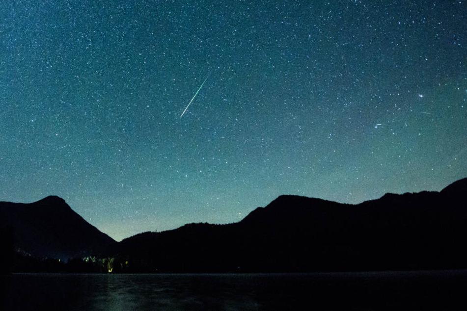 Eine Sternschnuppe leuchtet neben der Milchstraße am Himmel.