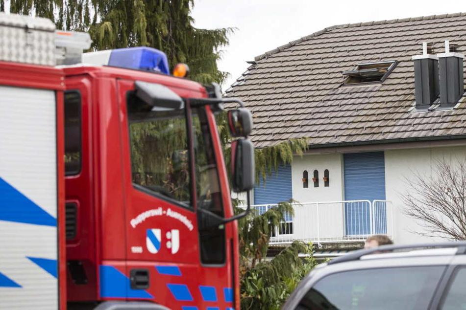 Ein Feuerwehrauto steht vor dem Haus, in dem vier Leichen mit durchgeschnittener Kehle gefunden wurden.