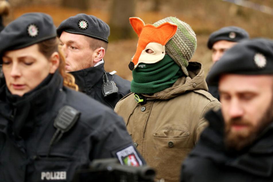 Ein Vermummter geht mit Polizisten zur Überprüfung der Personalien zu einem Einsatzfahrzeug.