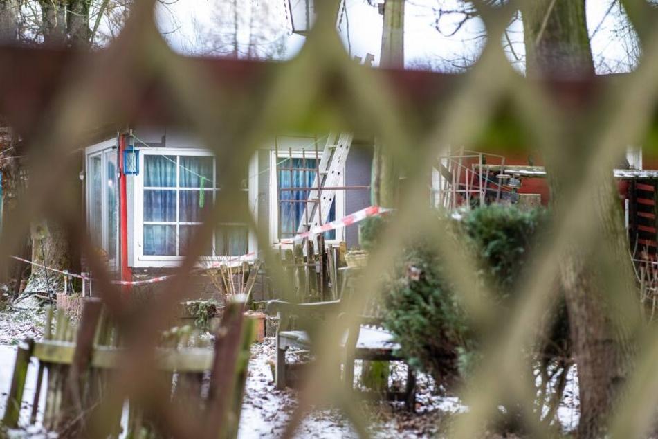 Blick durch einen Zaun auf ein Gebäude auf dem Campingplatz Eichwald, das mit einem Polizeiabsperrband versehen ist.