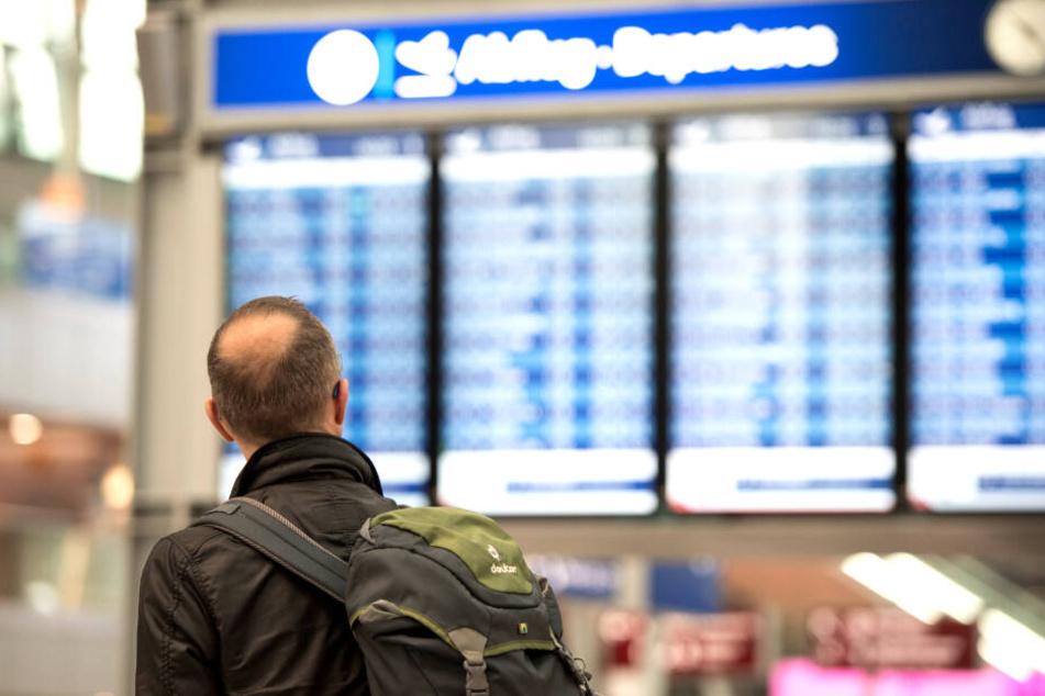 Ein Passagier blickt im Flughafen in Düsseldorf auf eine Anzeigetafel.