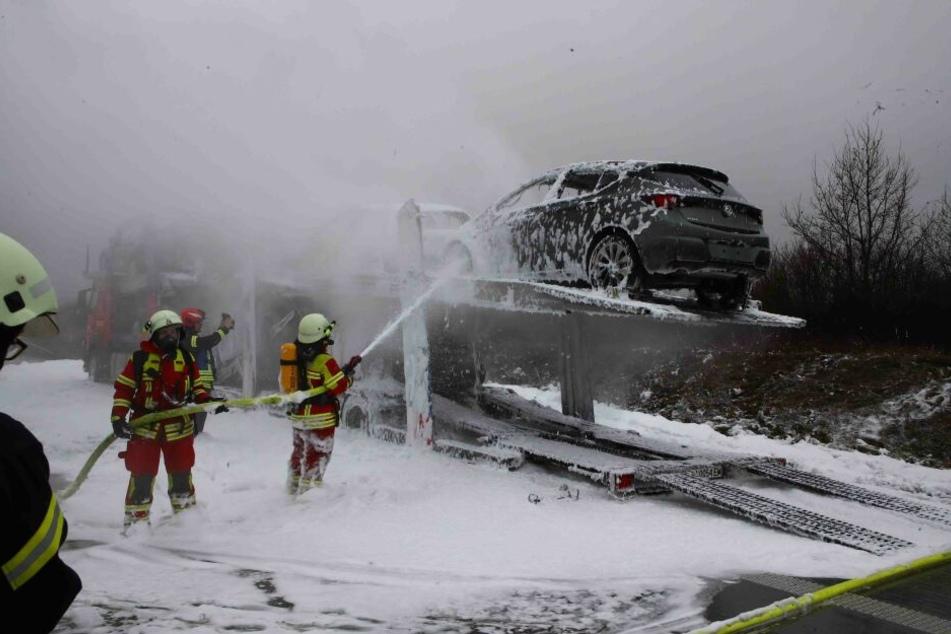 Feuerwehrleute löschen den brennenden Autotransporter.