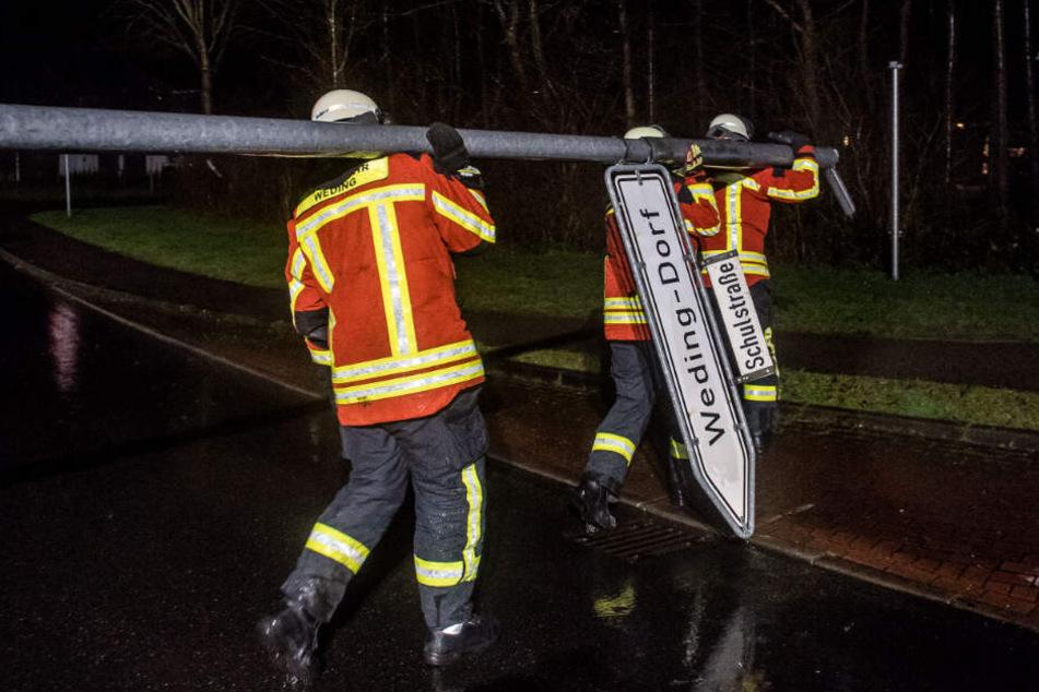 Feuerwehrleute tragen ein vom Wind umgewehtes Straßenschild weg.