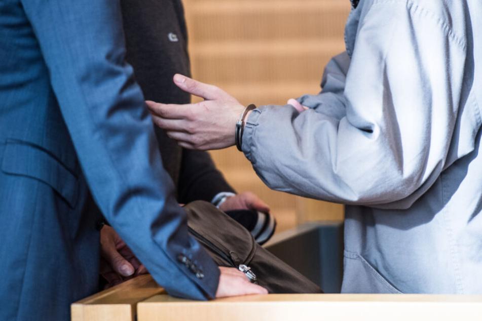 Der 28-Jährige steht mit Handschellen im Gerichtssaal.