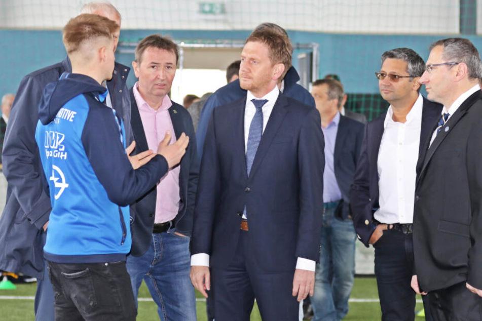 Sachsens Ministerpräsident Michael Kretschmer (Mitte) überzeugte sich persönlich vom Zustand der neu sanierten Trainingshalle und des Kunstrasenplatzes.