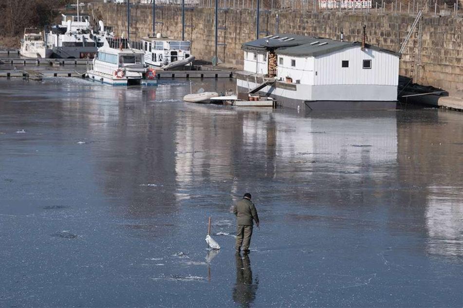 Ein Eisangler am zugefrorenen Hafenbecken.