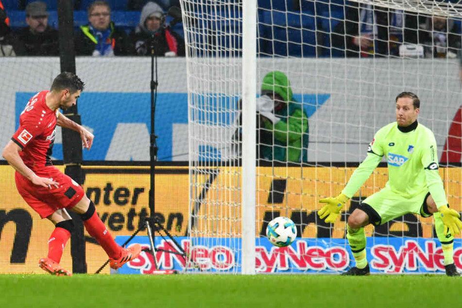Leverkusens Lucas Alario (links) schießt an TSG-Torwart Oliver Baumann vorbei - und erzielt das 0:3 für Leverkusen.