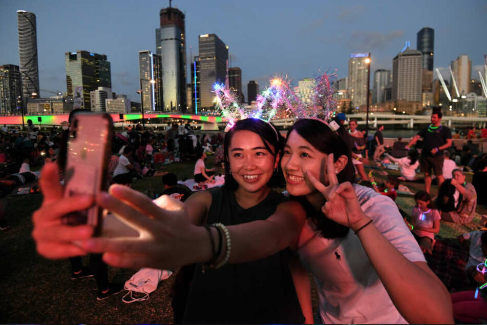Brisbane: Mizuki (l) und Tsubasa machen ein Selfie, während sie auf den Start der Feuerwerksshow zum Jahreswechsel im Stadtteil South Bank warten.