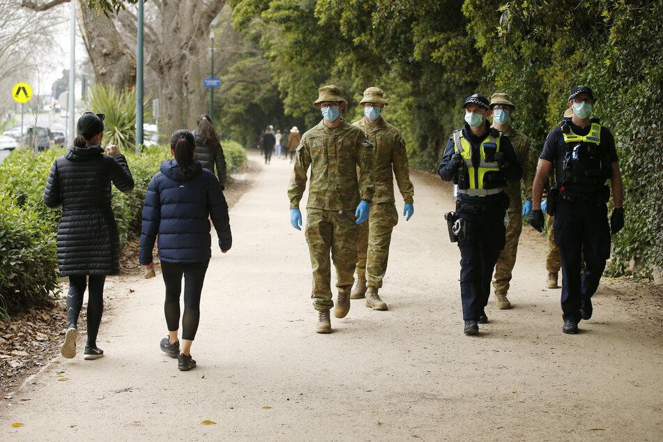 Die Zahl der Infizierten in Australien steigt an. Hier patrouillieren Polizisten und Verteidigungskräfte in einem Park in Melbourne.