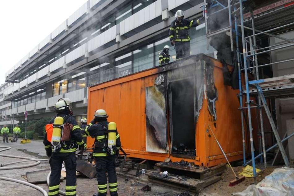 Einsatzkräfte löschen die brennenden Container.