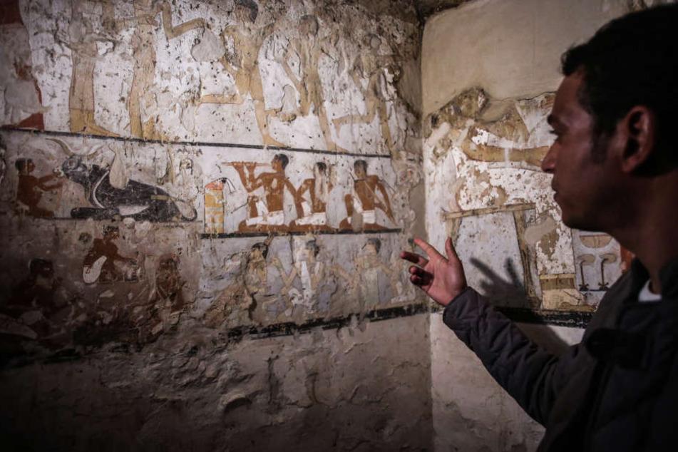 Ein Mitarbeiter der Ausgrabungen deutet auf die Wandmalereien in einem neu entdeckten Grab in der Nähe der Cheops-Pyramiden in Gizeh.