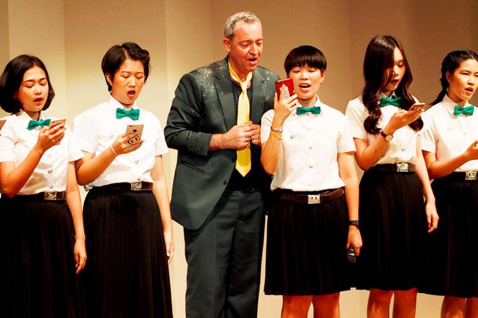 Der deutsche Kabarettist und Sänger Rainald Grebe (3.v.l) bei einem Auftritt mit thailändischen Studentinnen im Goethe-Institut von Bangkok.
