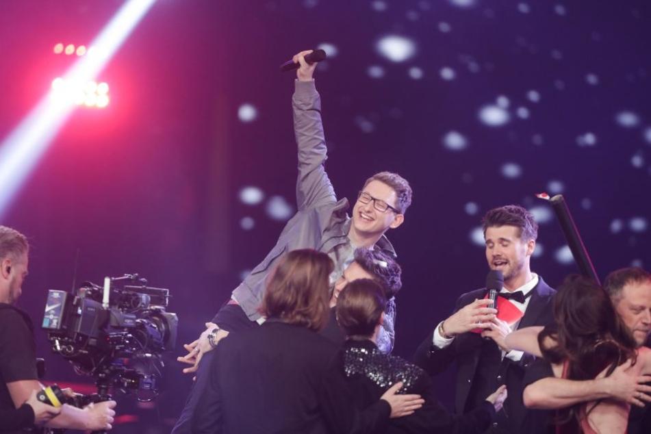 """Der Kandidat Samuel Rösch (M) jubelt über seinen Sieg bei der Castingshow """"Voice of Germany"""" auf der Bühne."""