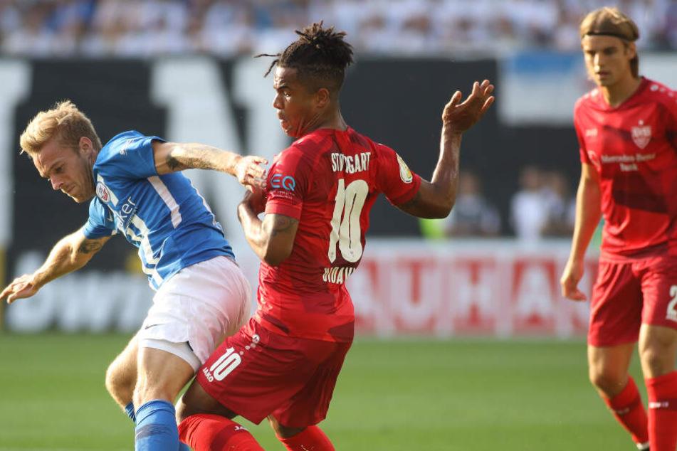 Rostocks Nils Butzen (l) kämpft mit Stuttgarts Daniel Didavi (M) um den Ball.