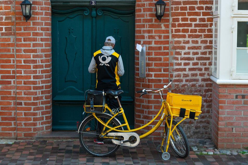 Ein Postbote fährt Briefe in der historischen Innenstadt von Lüneburg aus.