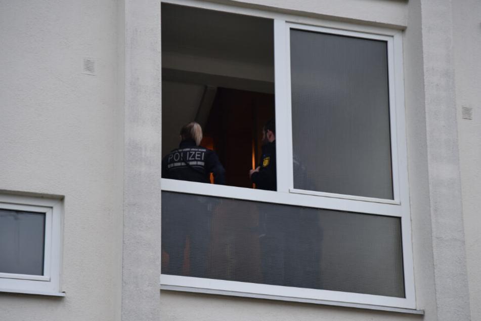 Polizisten im Treppenhaus des Mehrfamilienhauses.