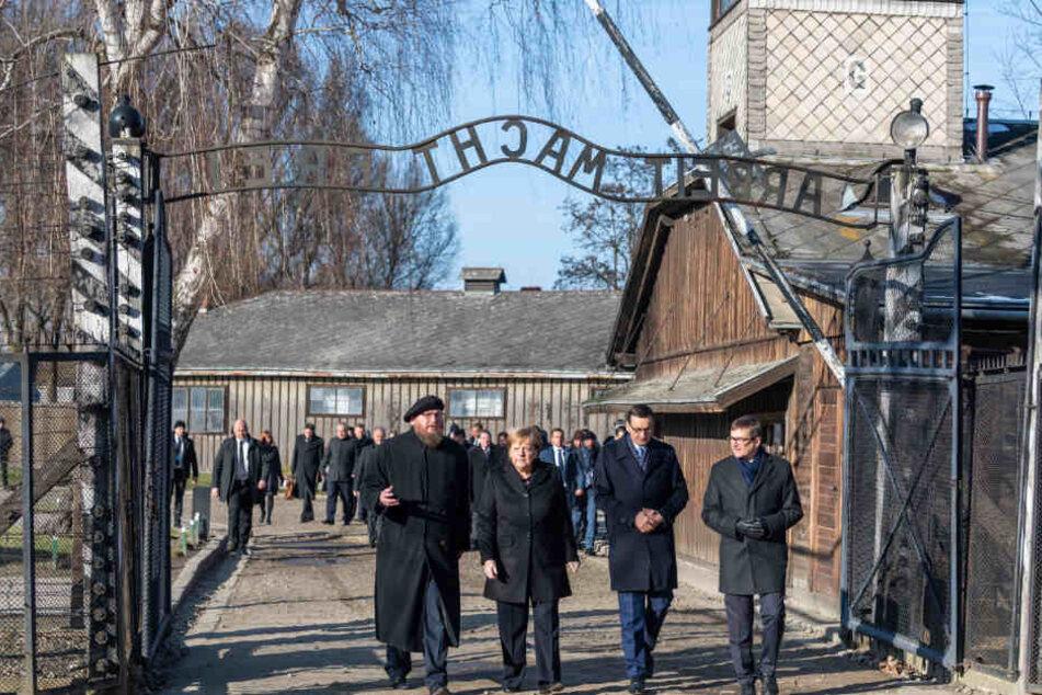 """Angela Merkel steht mit Mateusz Morawieckiund dem Direktor der Gedenkstätte, Piotr Cywinski unter dem Eingangstor mit dem Schriftzug """"Arbeit macht frei""""."""
