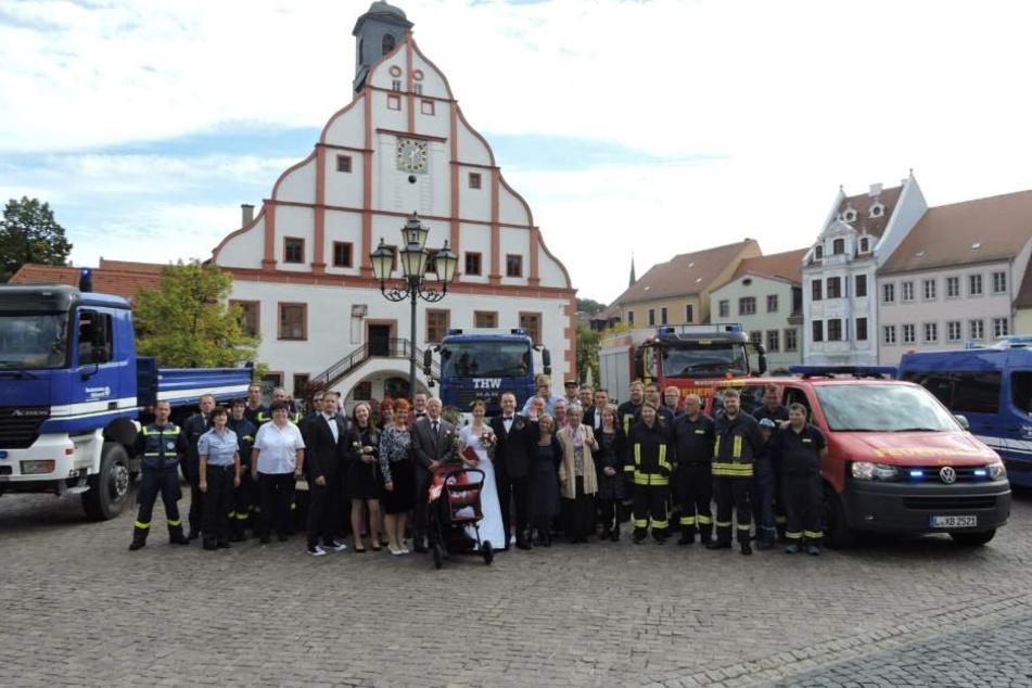 Eine ganze Menge wichtige Menschen: Familie und Freunde sowie Kameraden des Technischen Hilfswerks und der Feuerwehr beim Hochzeitsfoto. Davor liegt Töchterchen Alia im Kinderwagen.