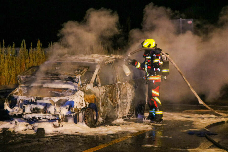 Ein Brandbekämpfer steht vor dem ausgebrannten VW.