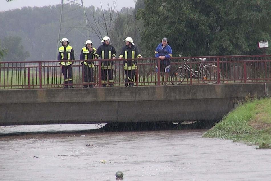 Kameraden der Feuerwehr schauen besorgt auf die Holtemme. Innerhalb weniger Stunden stieg das Wasser gefährlich an.