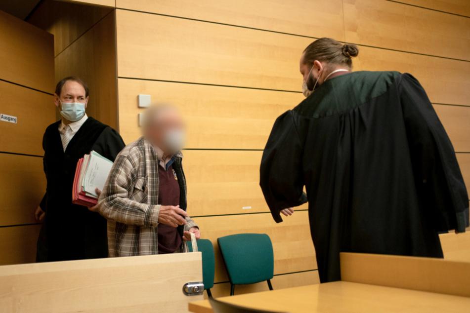Der Angeklagte (Mitte) wird von seinem Anwalt Norman Jacob (r.) in den Gerichtssaal geführt.