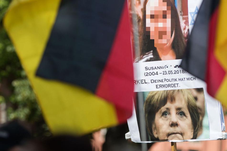 """Ein Teilnehmer der Kundgebung der Initiative """"Beweg was!"""" hält ein Plakat mit einem Bild der ermordeten Susanna und von Bundeskanzlerin Angela Merkel."""